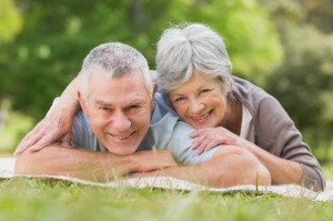 Portrait of a smiling relaxed senior couple lying in the park
